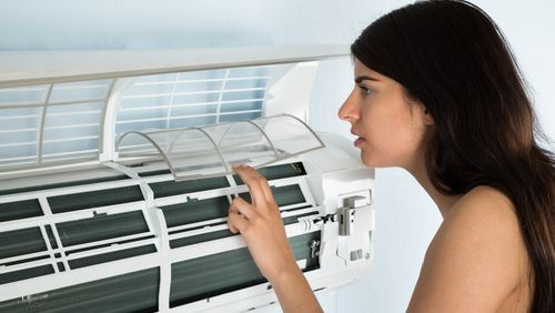 woman investigates broken air conditioner